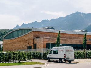 Dreifachsporthalle in Bad Reichenhall: Aluminiumstehfalz. Tonnendach mit 36m Spannweite. Verkleidung der Attika mit gefertigten Kasetten.