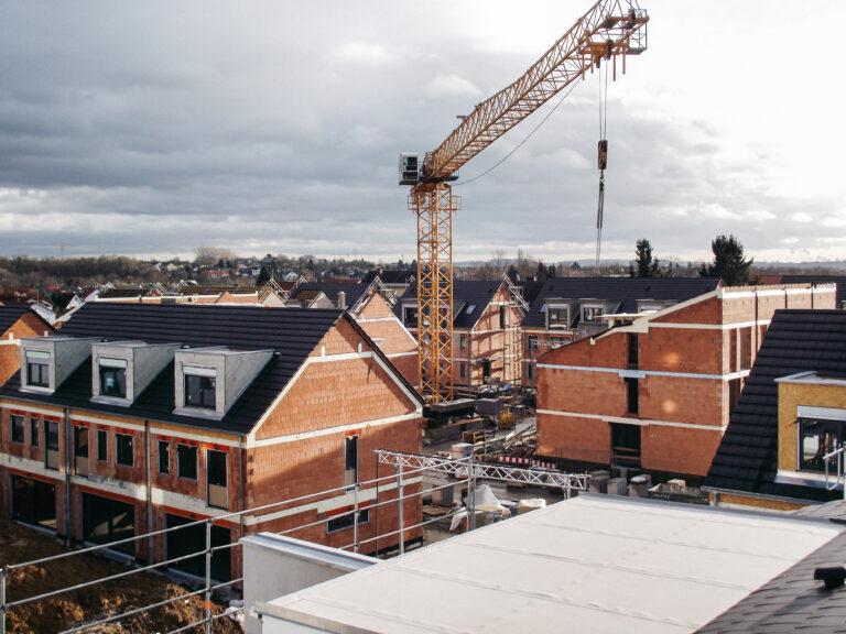 """Neubau von 86 Doppel- und Reihenhäusern im """"Fuchsloch"""" in Nieder-Erlenbach (Frankfurt a.M.). Zimmerarbeiten, Dacheindeckung mit Ziegeln, Terrassenabdichtung mit Terrassendielen."""