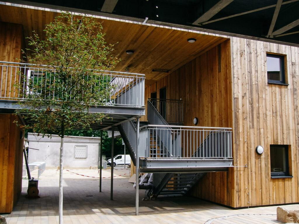 o16 – Übernachtungsstätte im Ostpark Frankfurt am Main: Flachdachabdichtung mit einer FPO-Bahn, Dachbegrünung und der Gestaltung der Fassade aus zweifarbig eloxiertem Edelstahlblech.